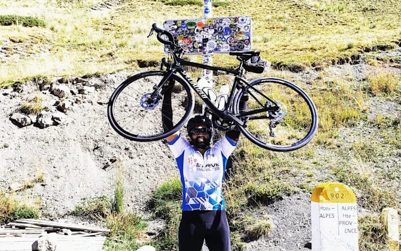 Asanka Pathiraja holds his bike above his head with a hillside behind him