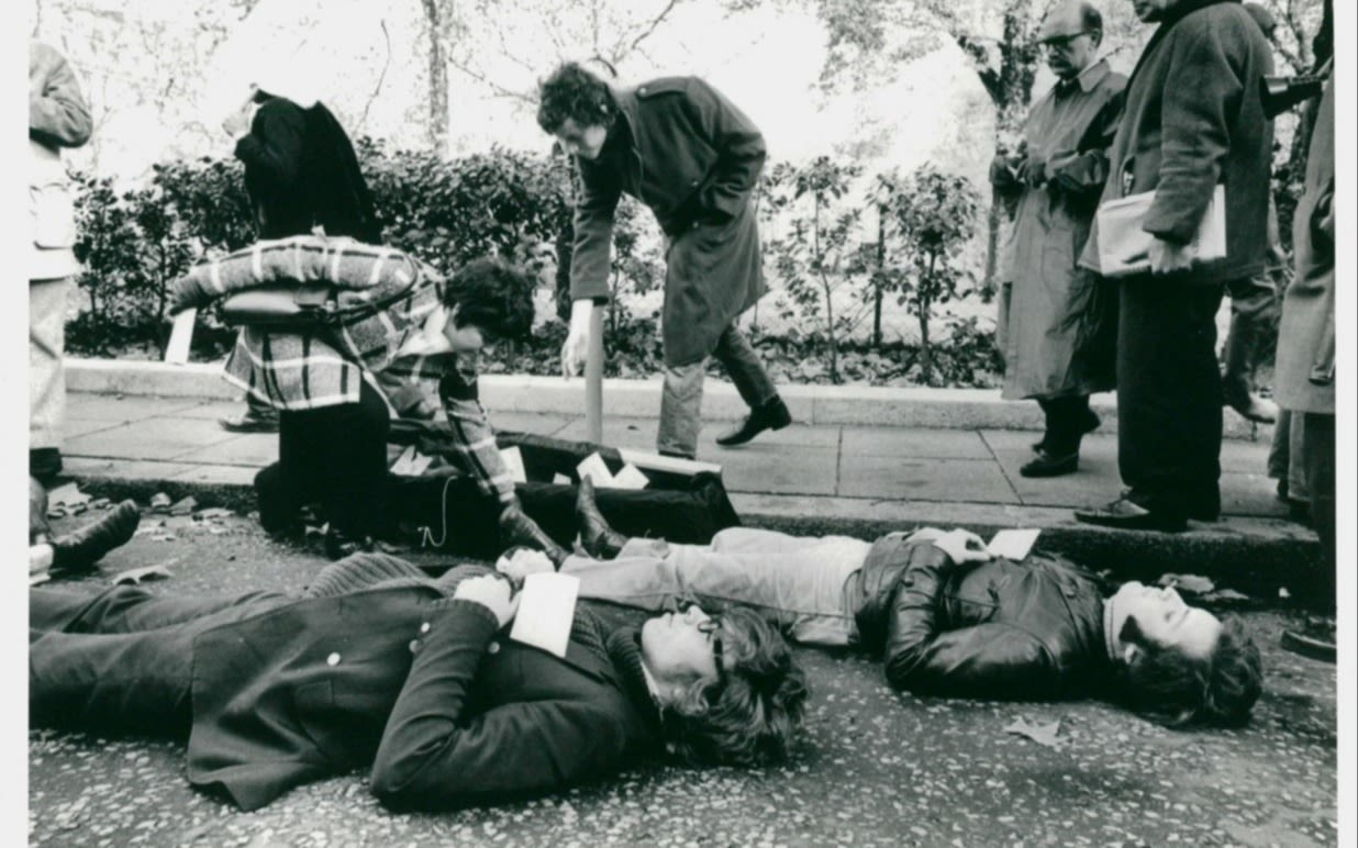 Black and white photo of a young Richard Branson and others lying down on the ground in protest