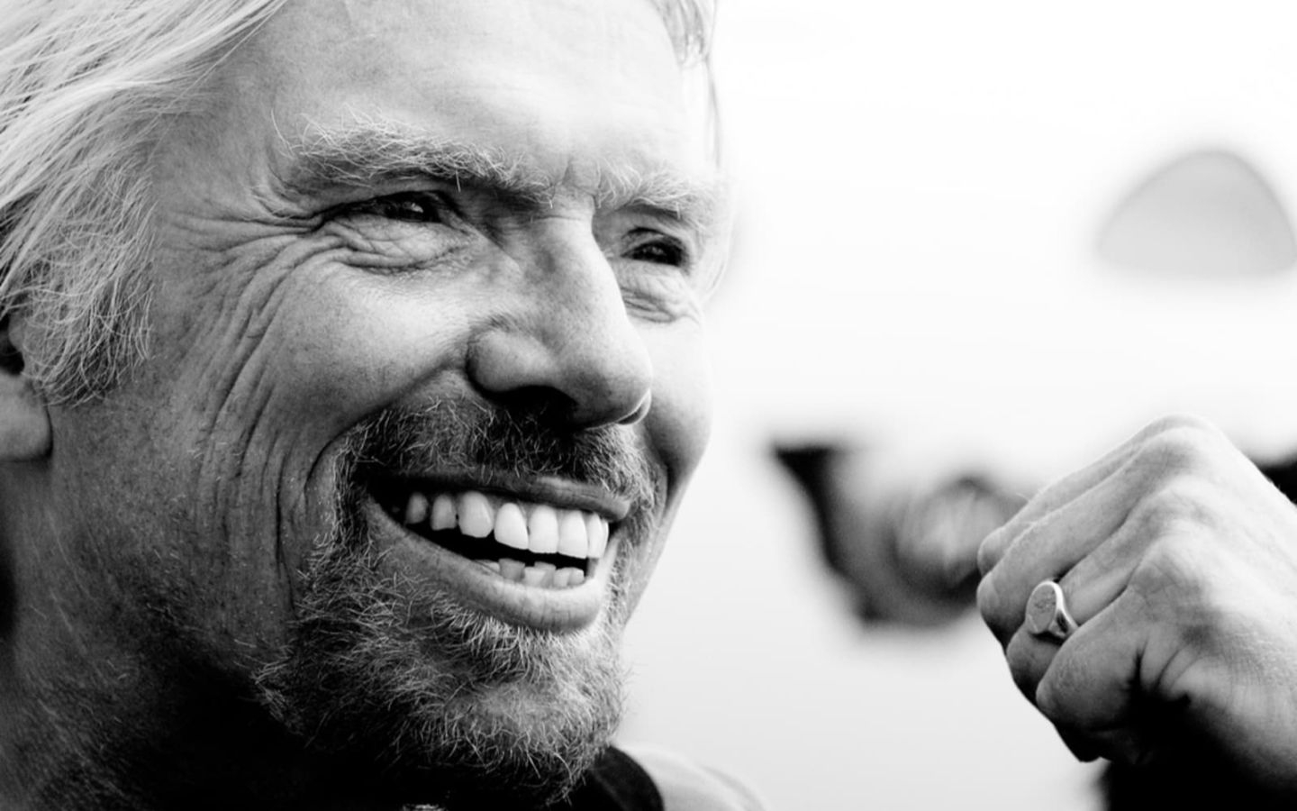Close up black and white photo of Richard Branson smiling with clenched fist