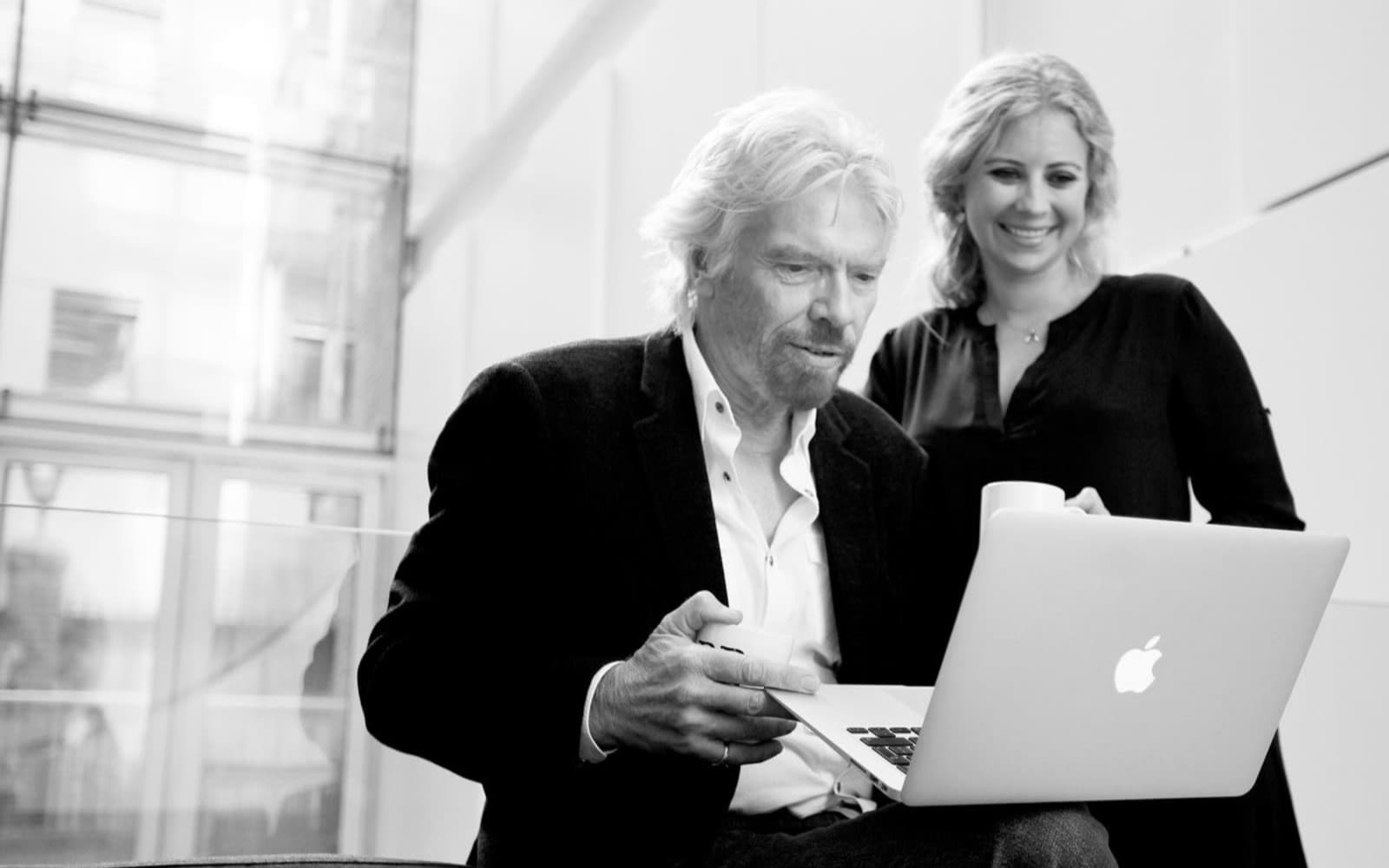 Black and white image of Richard using a laptop and Holly Branson standing next to him looking over his shoulder at the screen
