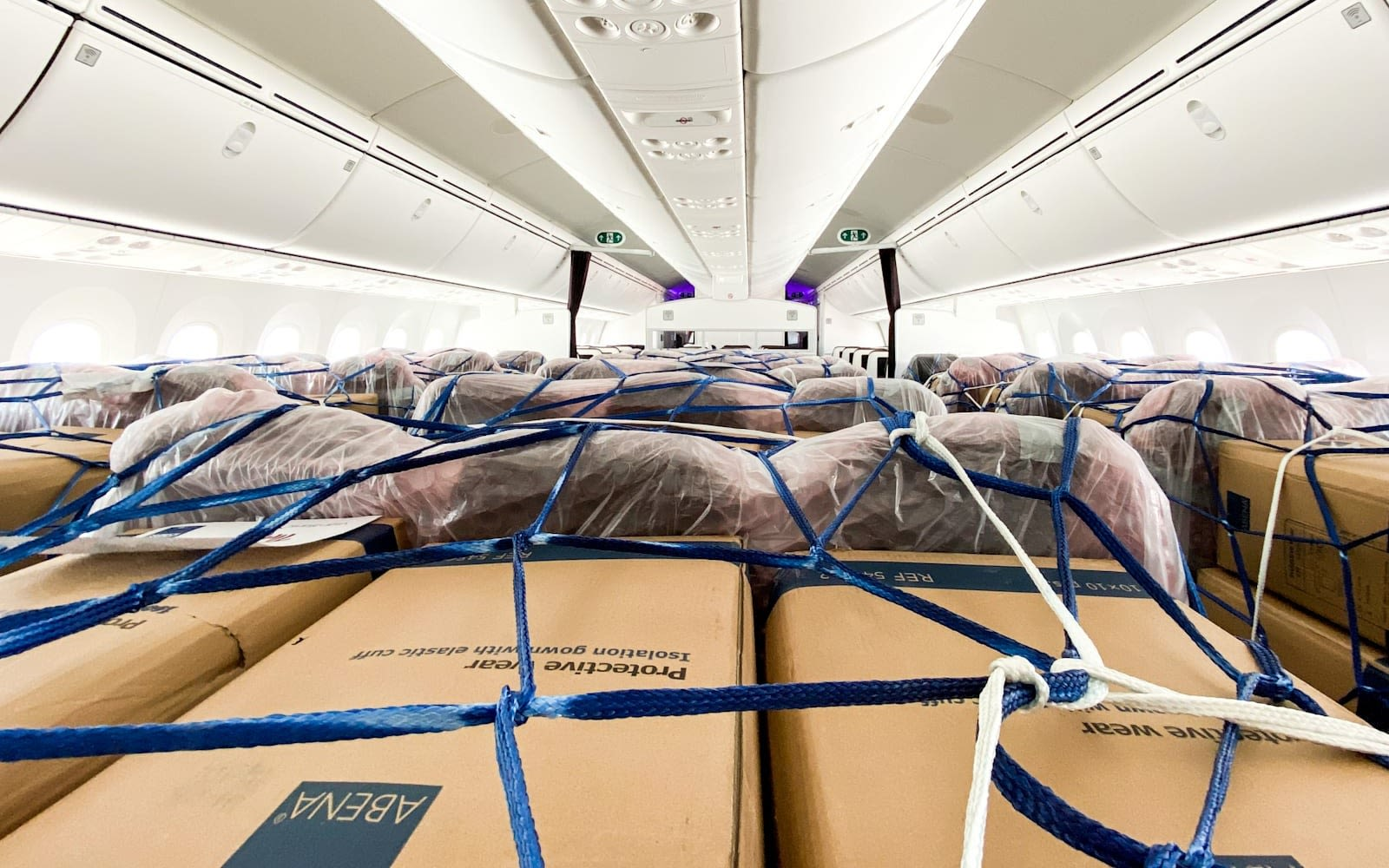 picure of boxed protective wear in the cargo area of a virgin plane ready for transport to help provide supplies for covid19
