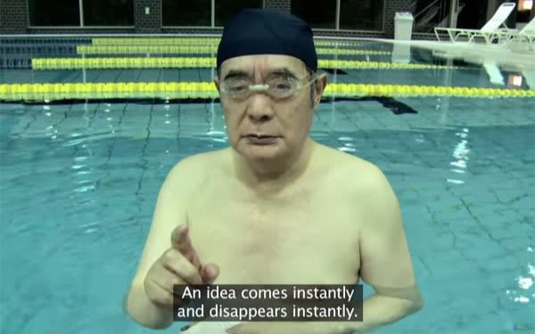 "A still taken from a video of Yoshiro Nakamatsu standing in a swimming pool pointing at the camera. The caption says ""An idea comes instantly and disappears instantly"""