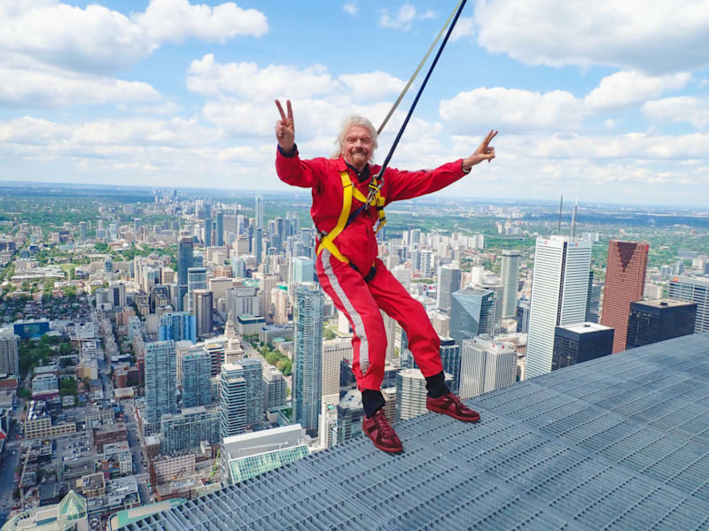 Richard Branson in red jumpsuit about to abseil down the Canada CN Tower