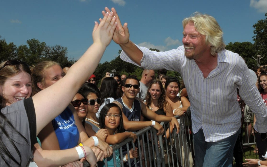 Richard Branson giving someone in a crowd a high five