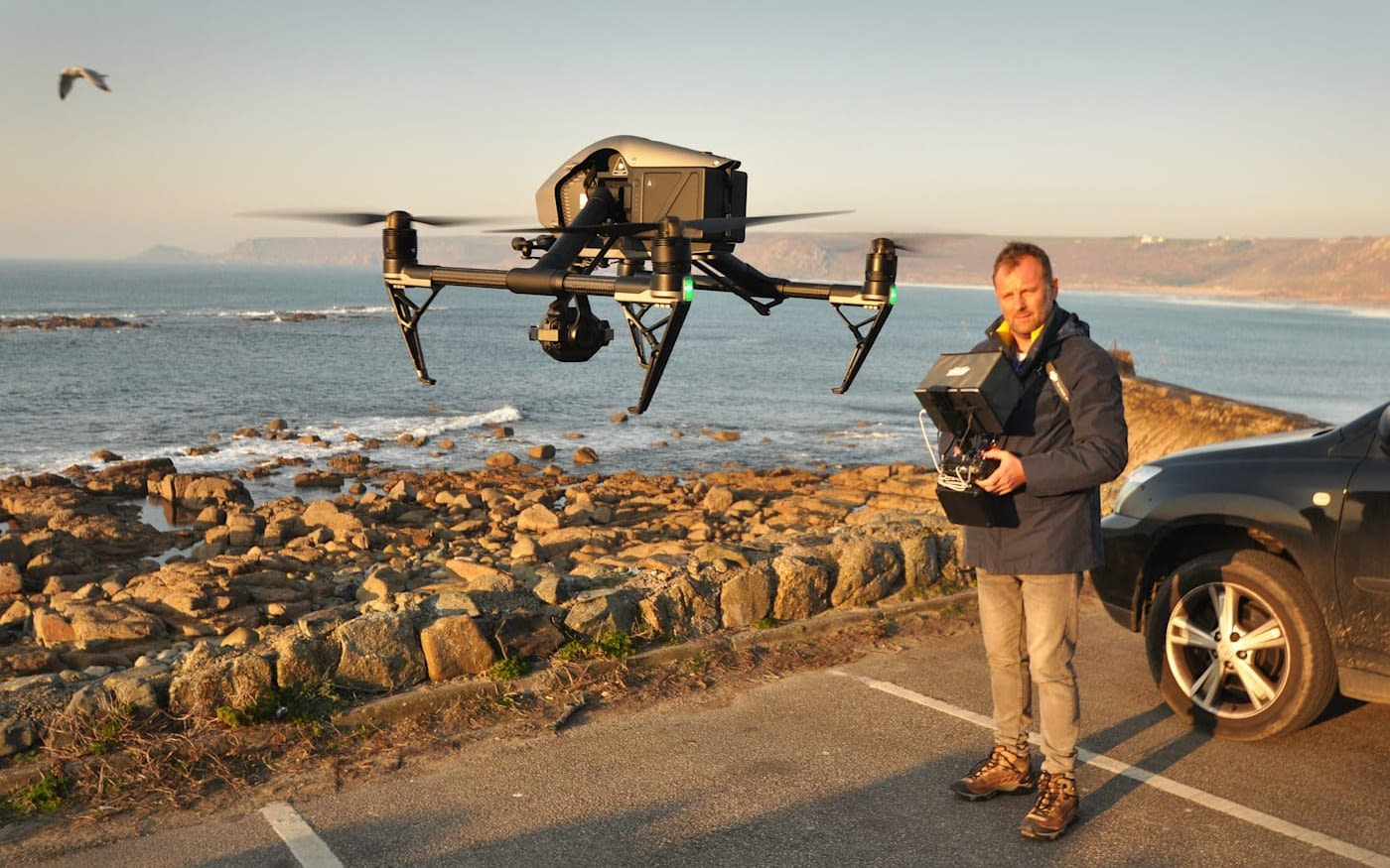 Drone hovering in a car park by the sea, with the pilot standing behind controlling the aircraft.