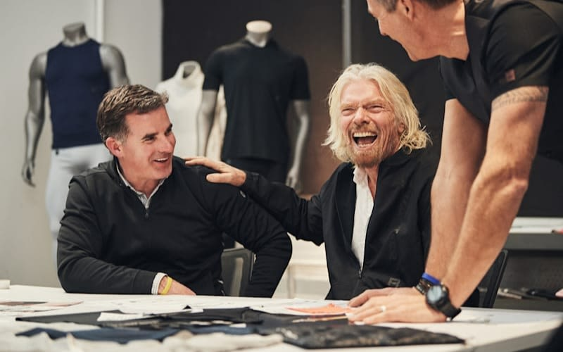 Richard Branson laughing with Kevin Plank and another man