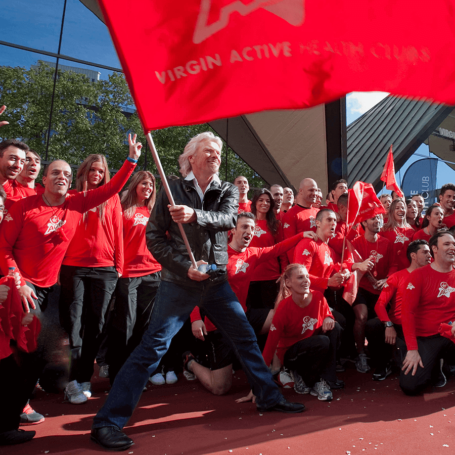 Richard Branson in a crowd waving a big Virgin Active flag