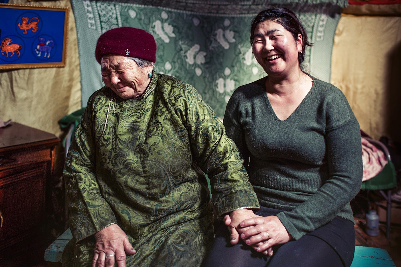 Two women holding hands and laughing in Mongolia