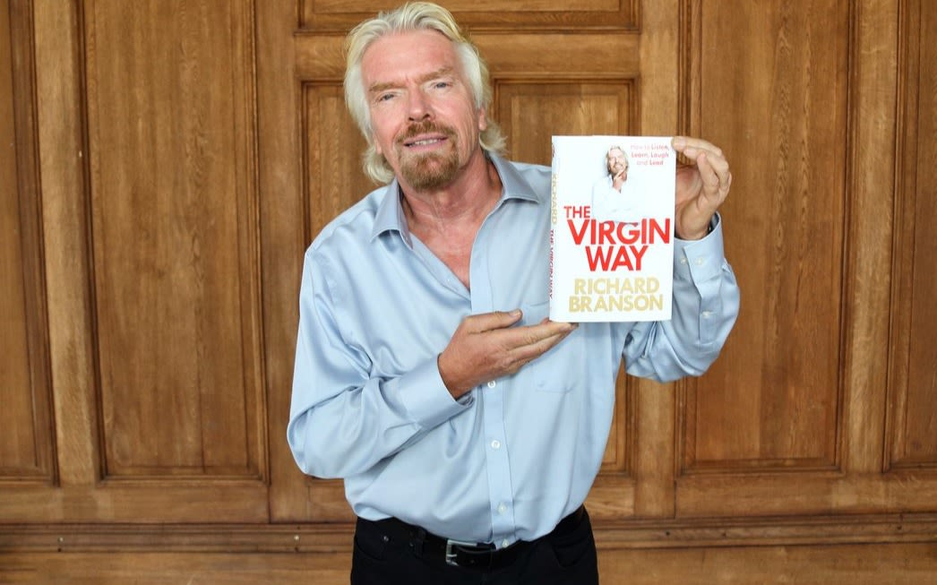 Richard Branson holding a copy of his book - The Virgin Way