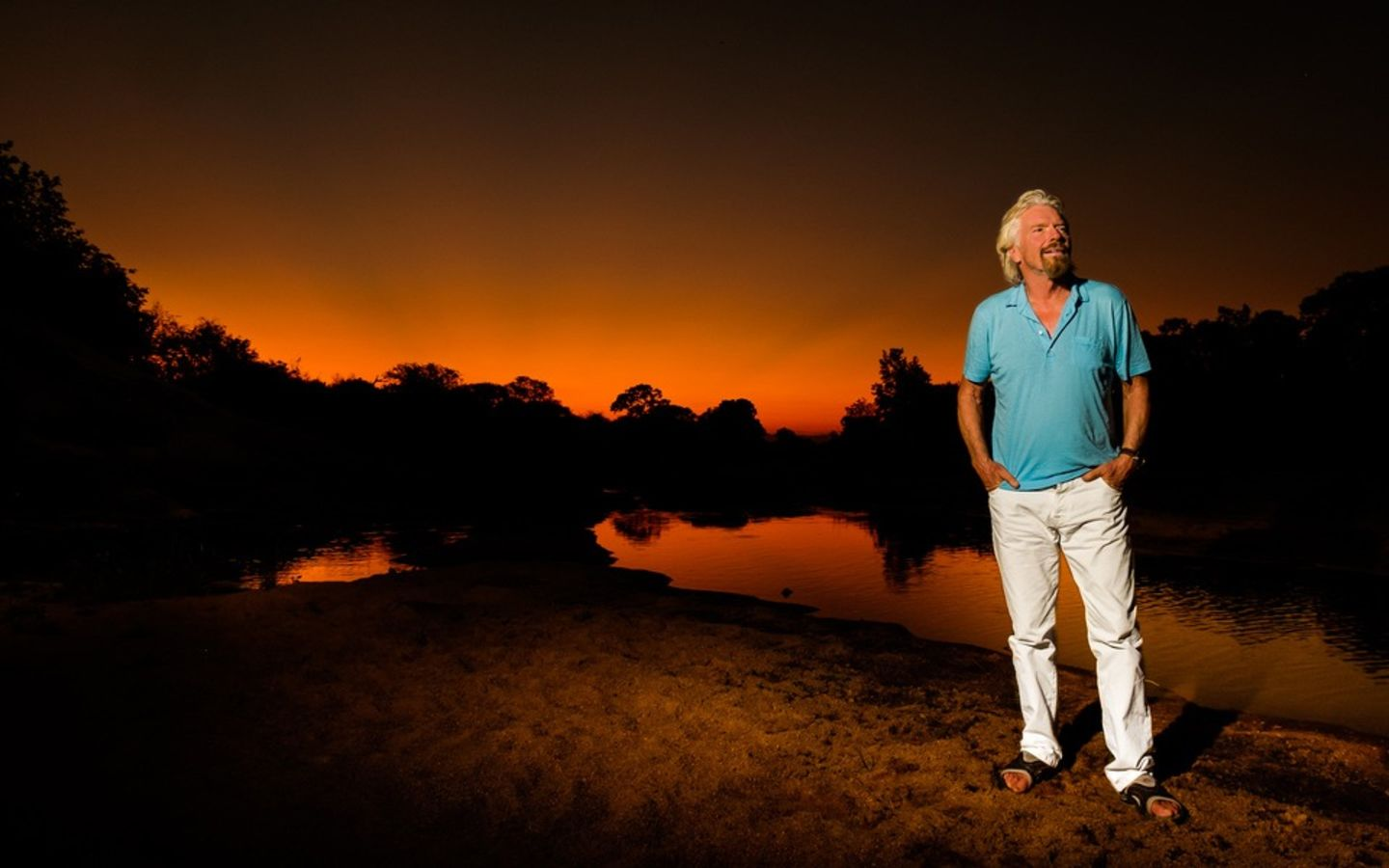 Richard Branson with his hands in his pockets and an orange and black sunset behind him