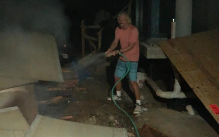 Richard Branson wearing pink tshirt and aiming a hose of water at  boxes on the Island of Necker after the fire