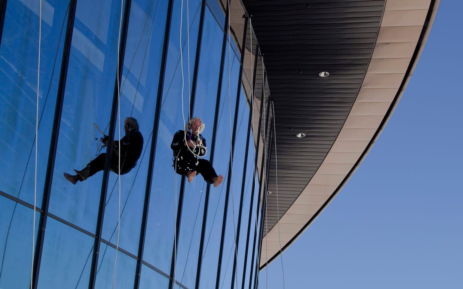 Richard Branson abseiling down a glass building