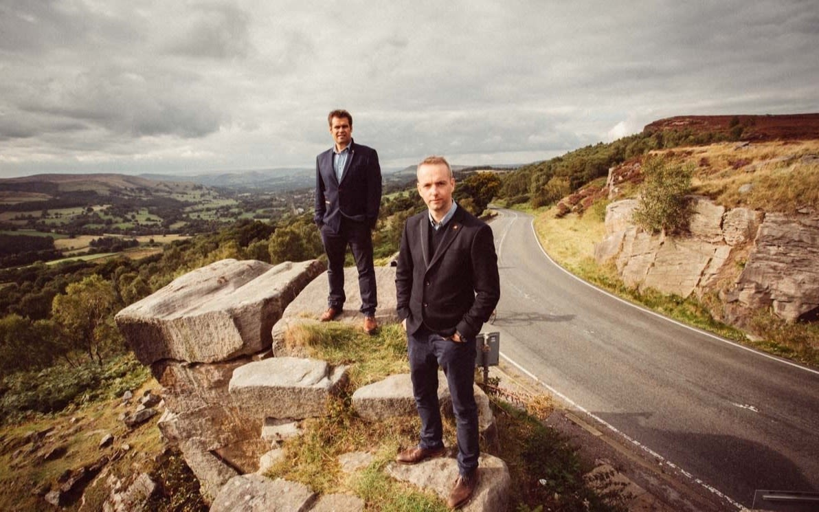 Pete Lindsay and Dr Mark Bawden wearing dark suits, stand beside each other on the edge of a cliff, beside a road