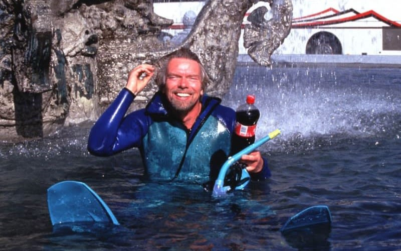 Richard Branson, floats in a pool smiling, holding a bottle of Coca Cola and a snorkel in his arm.  He is wearing a blue wet suit, complete with fins.