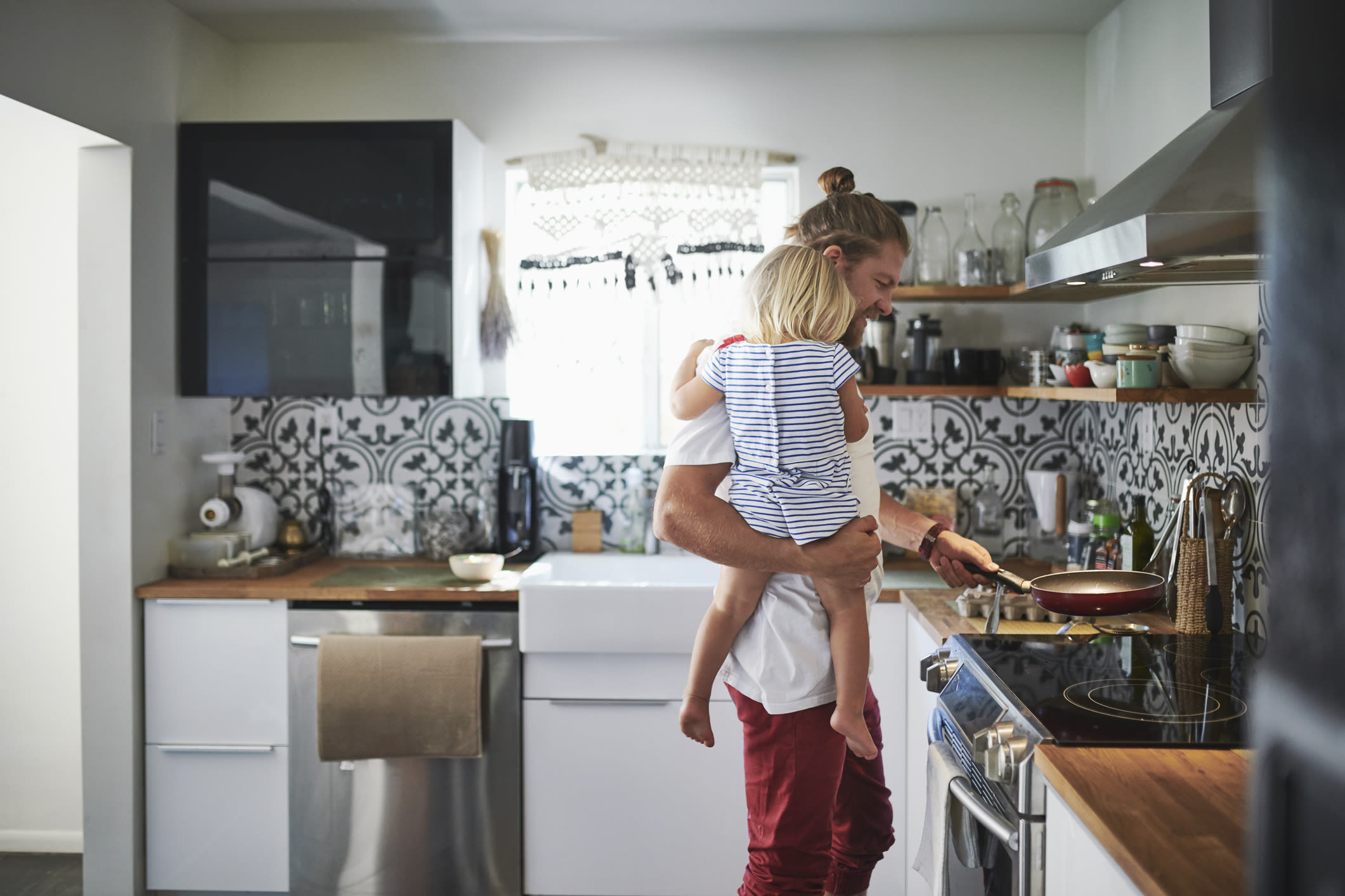 A man holding his daughter while cooking in the kitchen