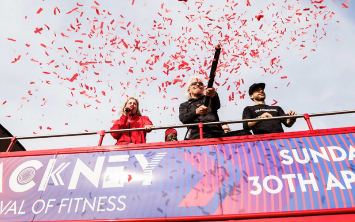 Richard Branson fires a confetti cannon from a double decker bus at Virgin Sport's Hackney Festival of Fitness
