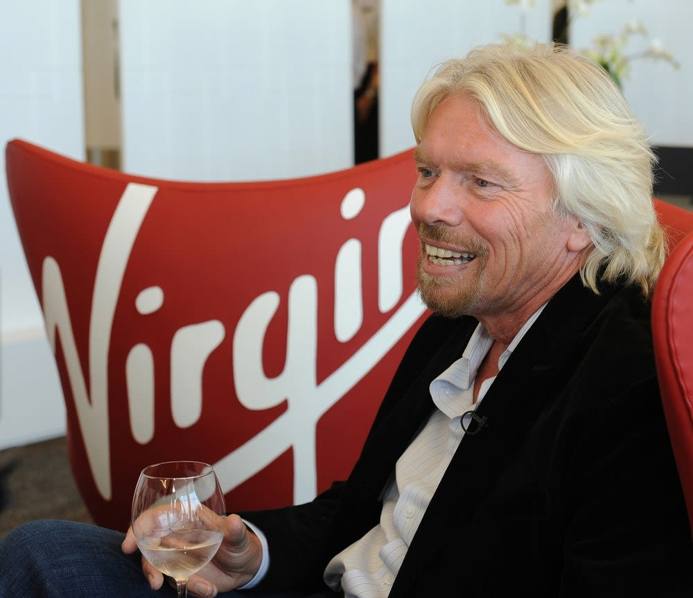 Richard Branson sitting on a chair, holding a glass of wine, with the Virgin logo on a cushion behind him