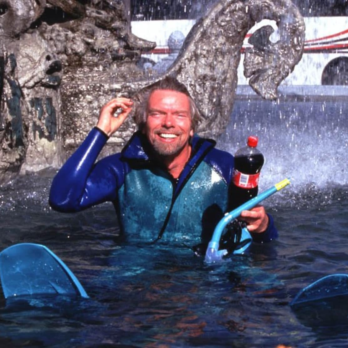 Richard Branson in a wet suit sitting in a fountain with a Virgin Cola bottle