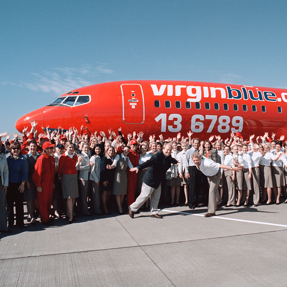 Richard Branson and a large group of Virgin Blue employees standing in front of a Virgin Blue aeroplane