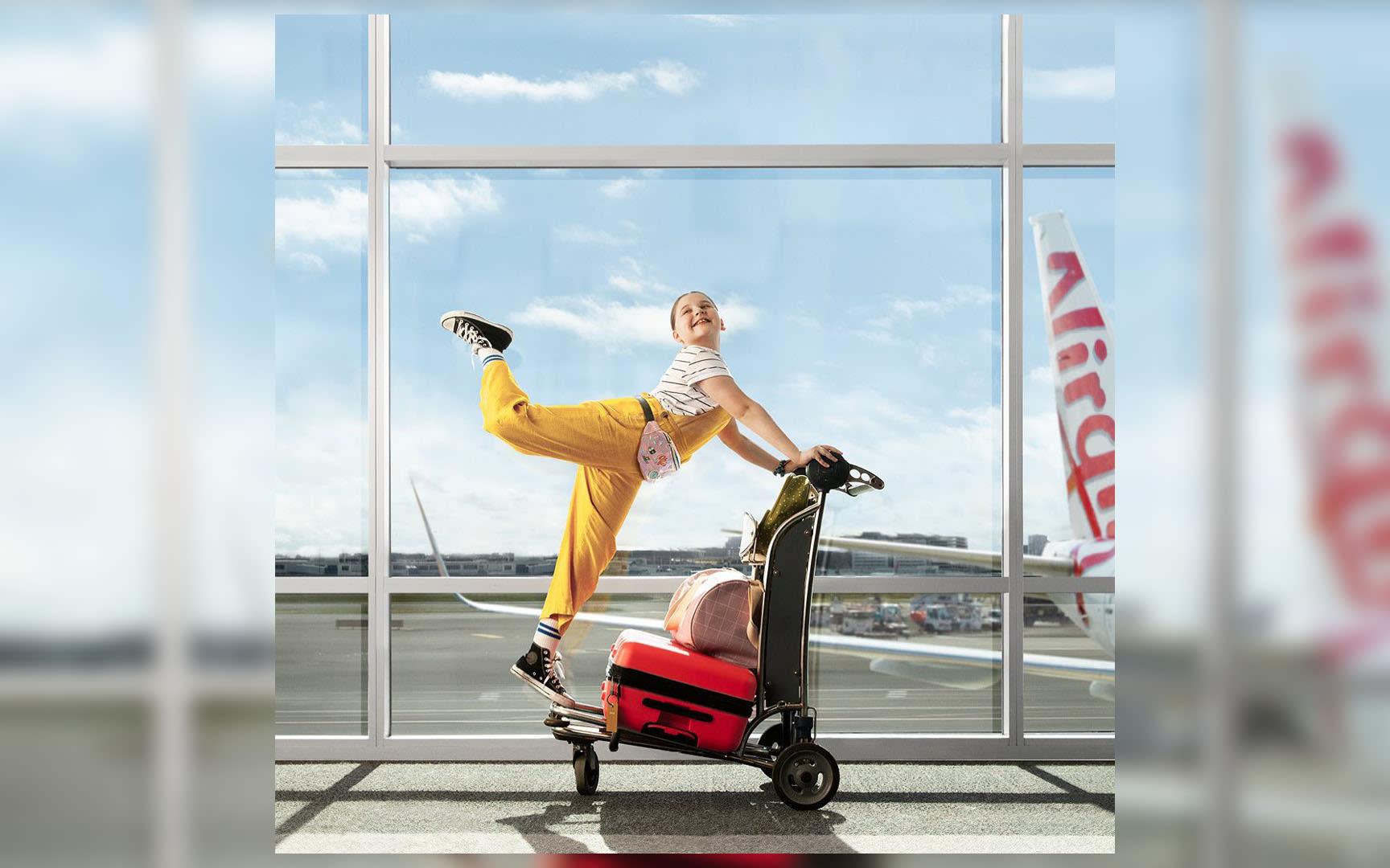 A girl in a yellow jumpsuit dances on a luggage trolley