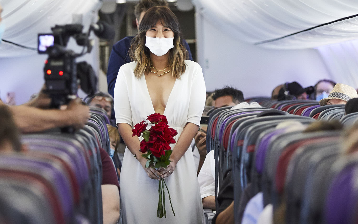 Elaine Tiong walks down the aircraft aisle wearing a white dress, holding a bunch of red roses