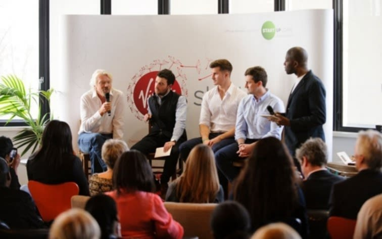 Richard Branson speaking into a microphone on a panel with 3 other men.