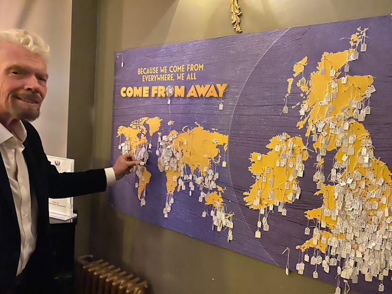 Richard Branson in front of a board that reads 'Because we come from everywhere, we all come from away' with the world map and several pinned pieces of paper