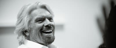 Black and white close up photo of Richard Branson laughing
