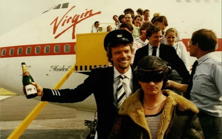 Richard Branson dressed as a pilot in a line of people exiting a Virgin Atlantic plane