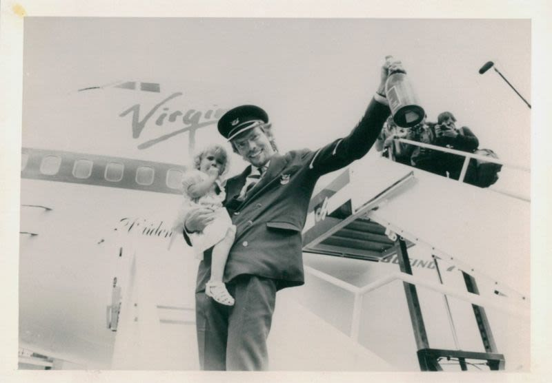 Black and white photo of Richard Branson dressed as a pilot holding Holly Branson in front of a Virgin plane
