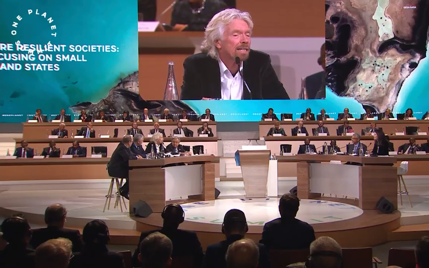 Several images of the One Planet Summit. One is of Richard Branson speaking, one is of the attendees sitting at tables, one is a meteorological image