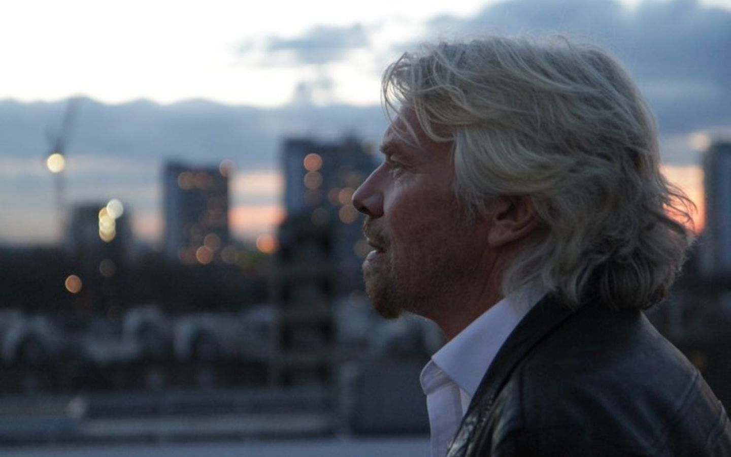 Side profile of Richard Branson looking pensive with sky and buildings in the background