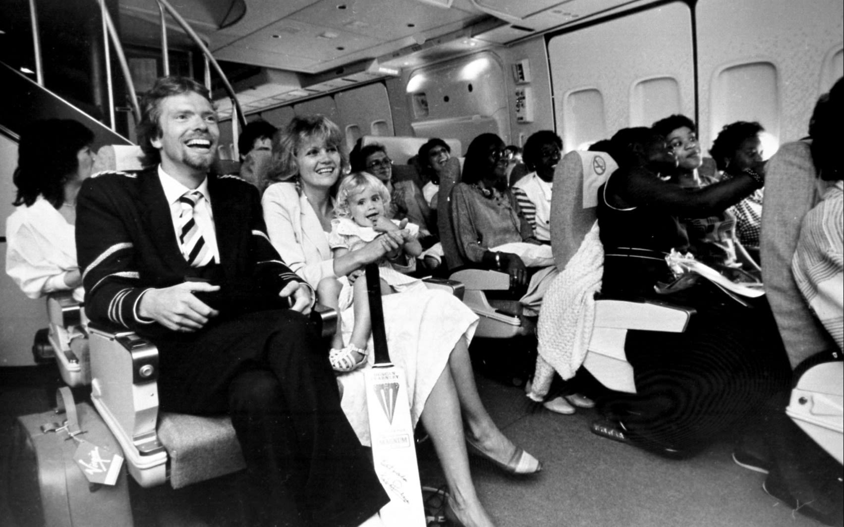 Black and white photo of Richard Branson, Joan and Holly sitting in a Virgin Atlantic plane