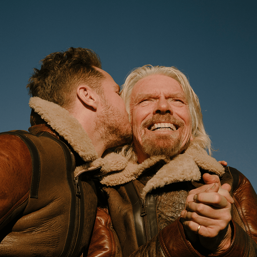 Richard Branson and his son Sam Branson embracing and looking happy