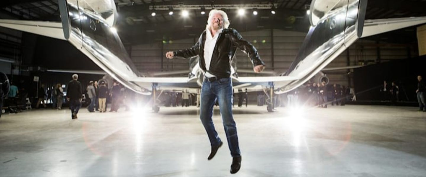 Richard Branson jumps in celebration in front of Virgin Galactic's VSS Unity