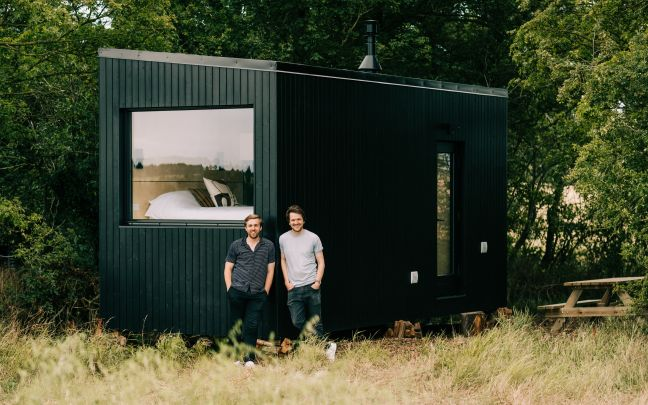 Ben Elliott and Hector Hughes, founders of Unplugged, stand outside a green cabin