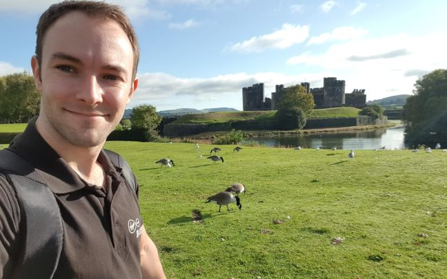 Lewis stands by a castle moat.
