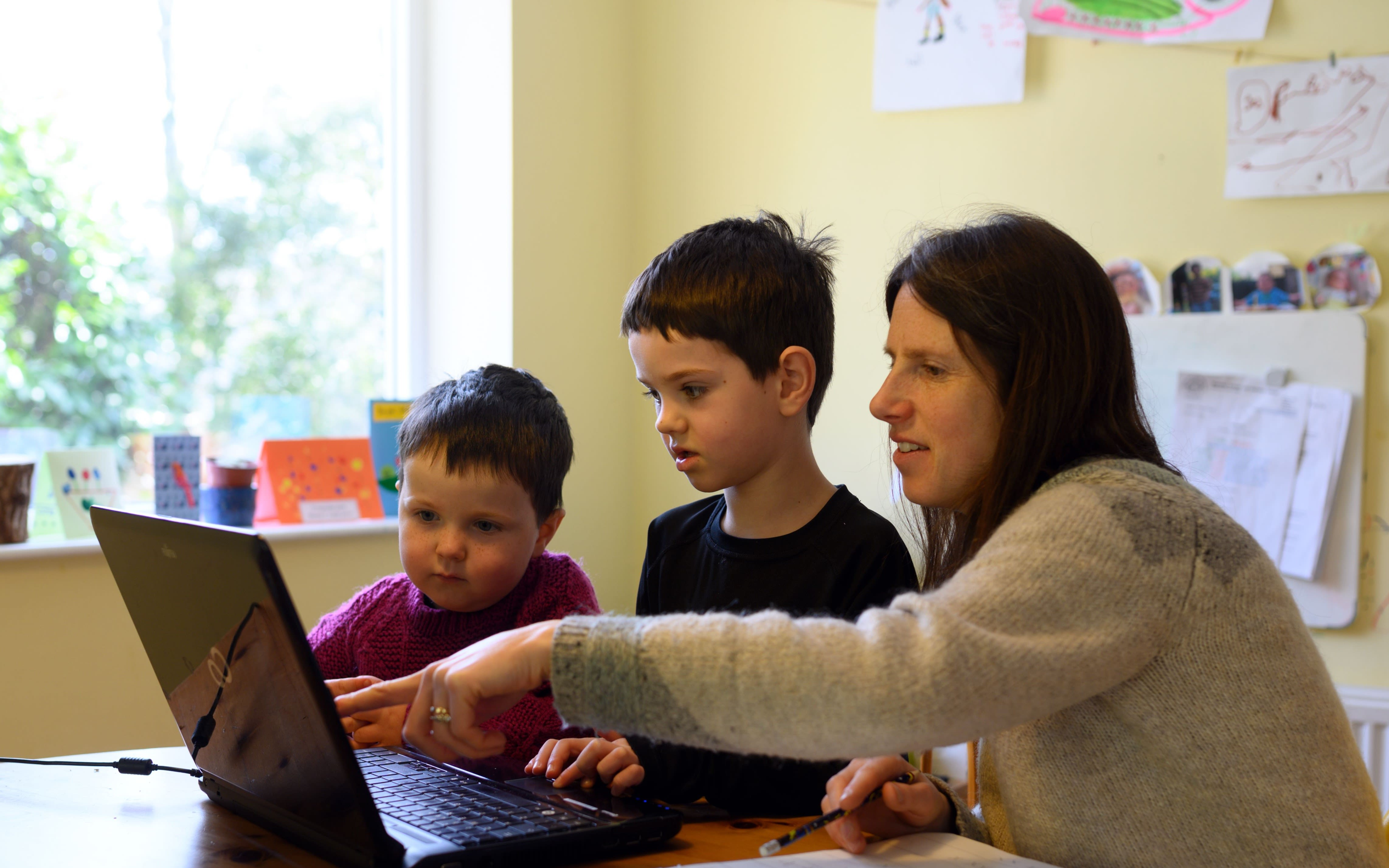 A mum helps her two sons with homeschooling