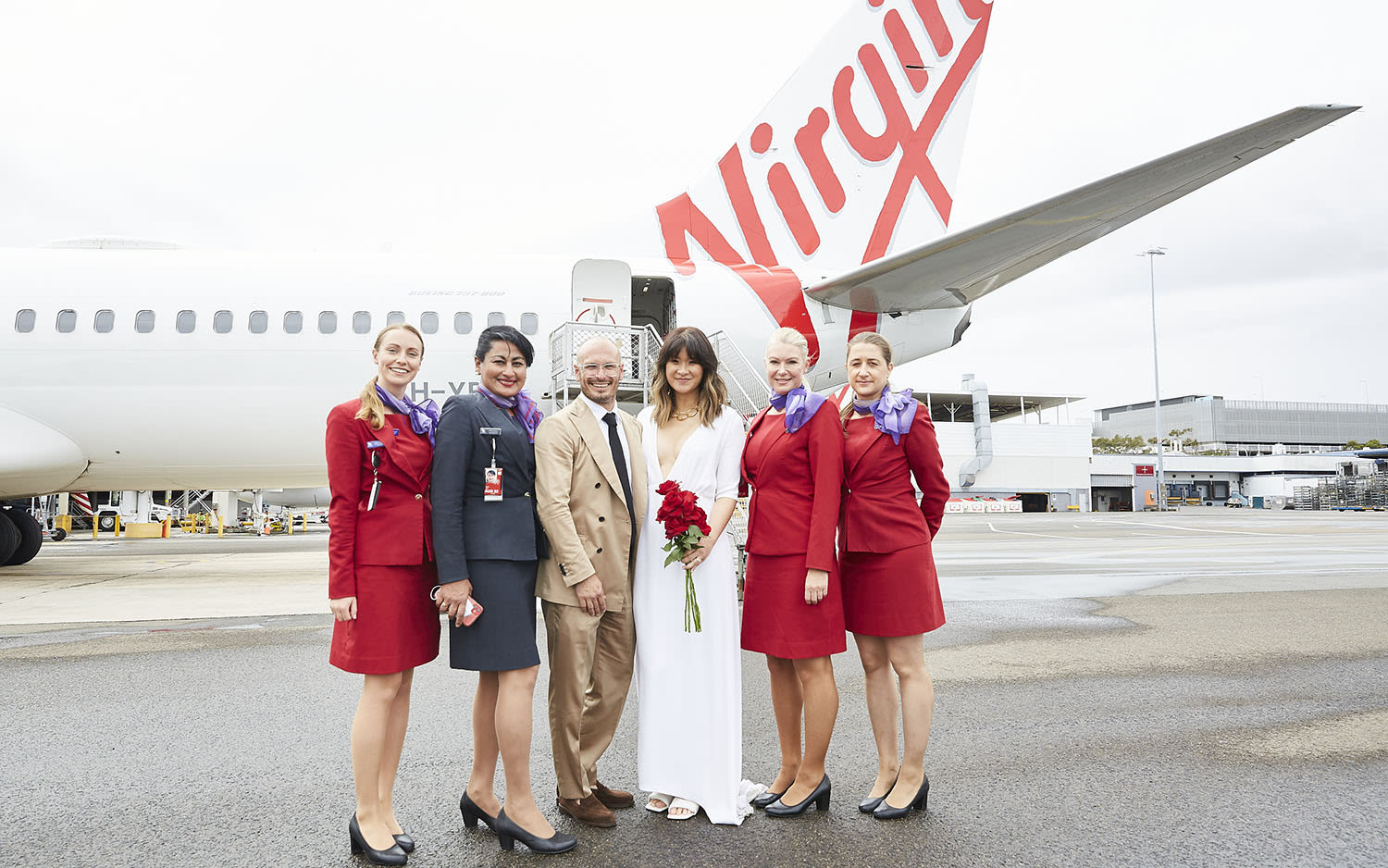Elaine and Luke Serdar stand outside the plane with the cabin crew of the flight on which they were married