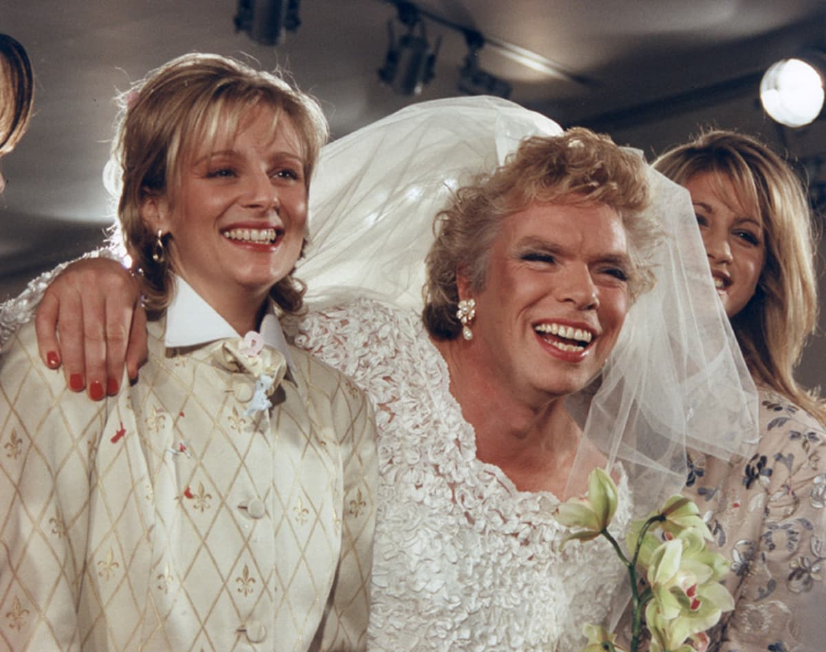 Richard Branson dressed in a veil and wedding dress, between two women, all smiling