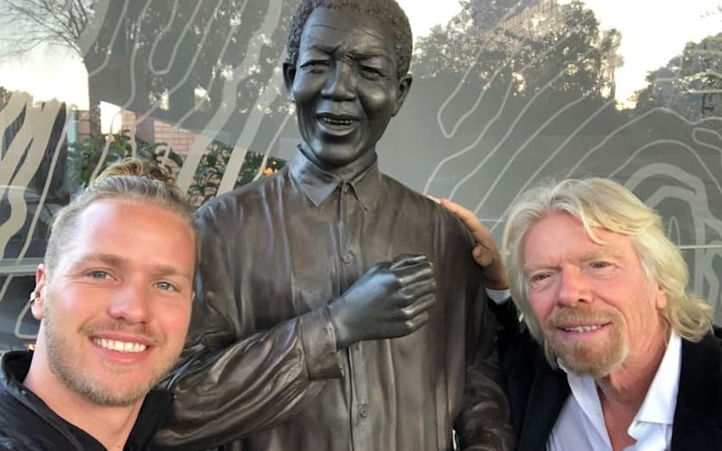 Richard and Sam Branson posing with a statue of Nelson Mandela