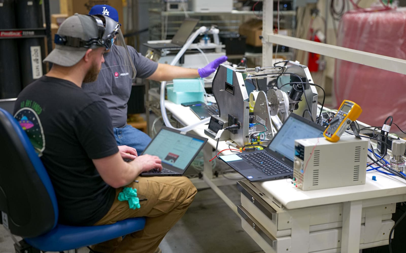 picture of 2 men sat at a work bench with 2 laptops both wearing visors look to be testing a ventilator in the process of being made
