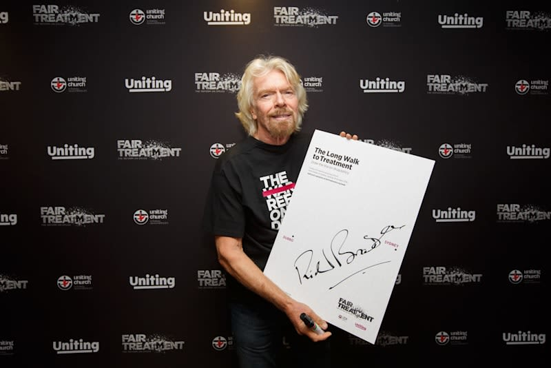 Richard Branson holding up a large piece of paper with his signature at the launch of Fair Treament in Sydney