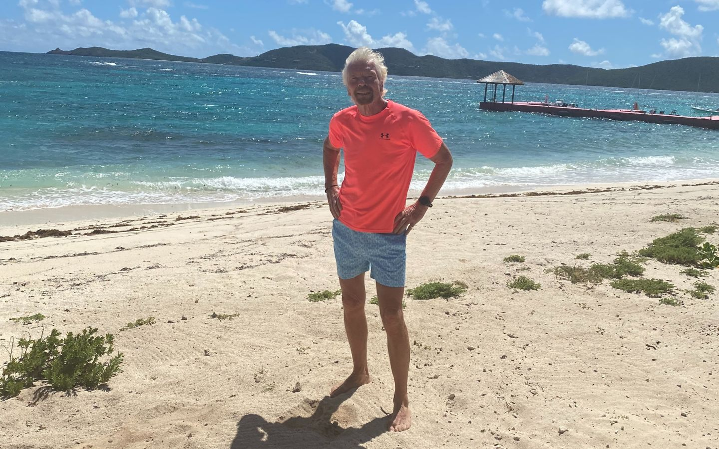 Richard Branson standing on the beach about to go for a swim