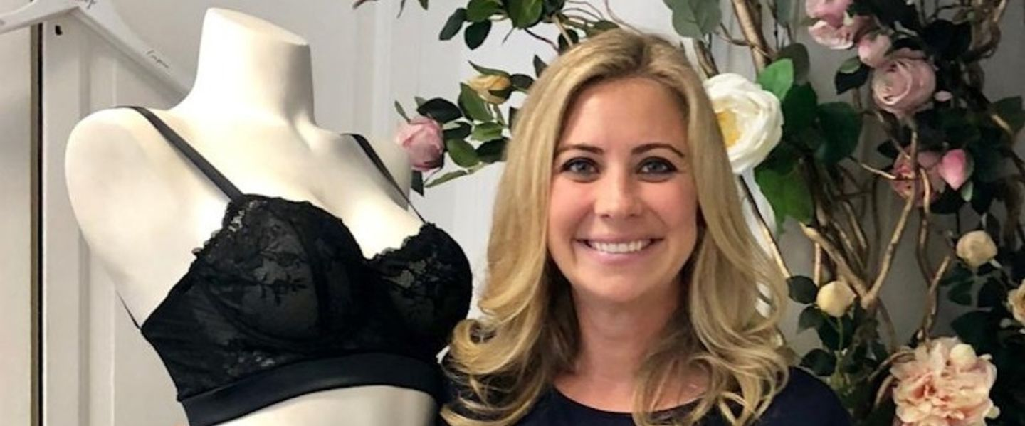 Holly Branson smiling at the camera, next to a mannequin wearing a black bra and in front of a wall with flowers climbing up it