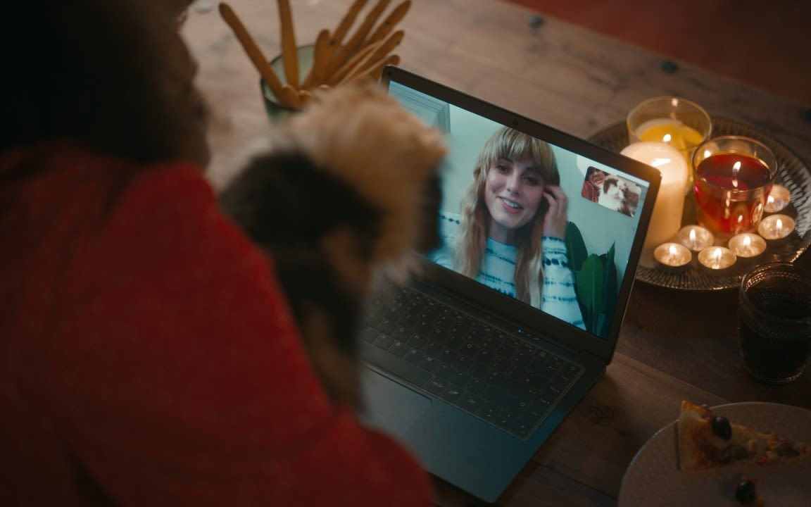 A woman and a cat on a video call with another woman, with candles in the background