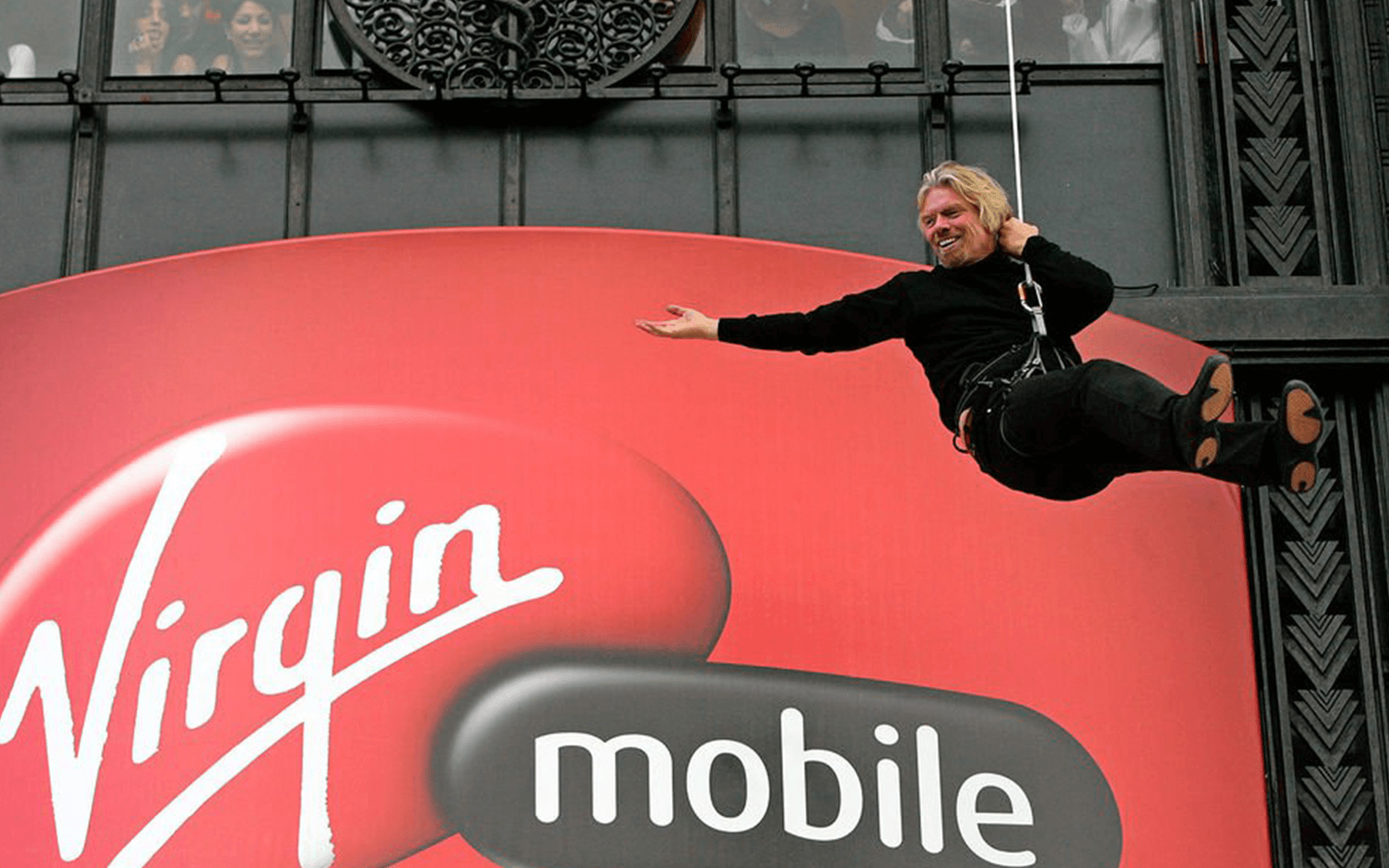 Richard Branson abseiling down a building with a giant Virgin Mobile logo on it