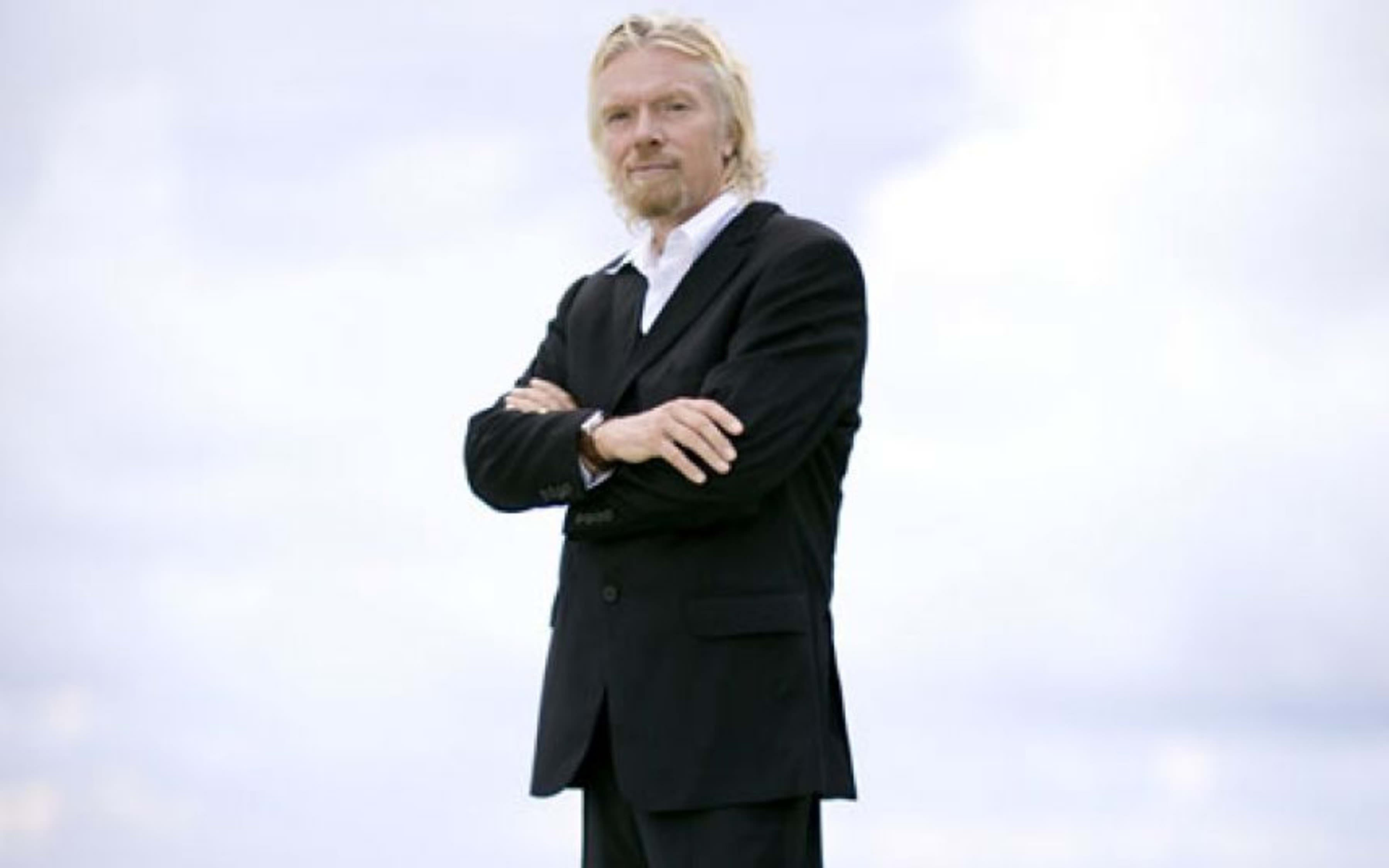 Richard Branson, arms folded, standing looking at the camera