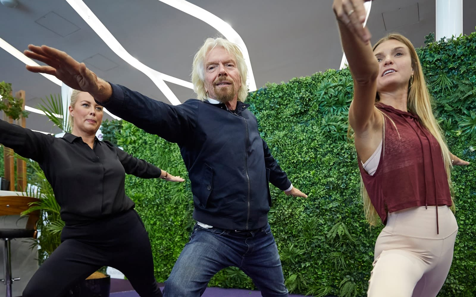 Richard Branson practices yoga with two female instructors in the Virgin Australia lounge