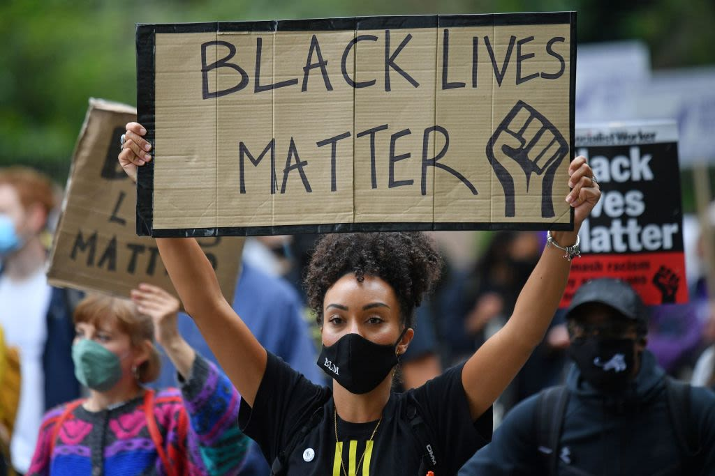A Black woman holds a Black Lives Matter sign at a protest